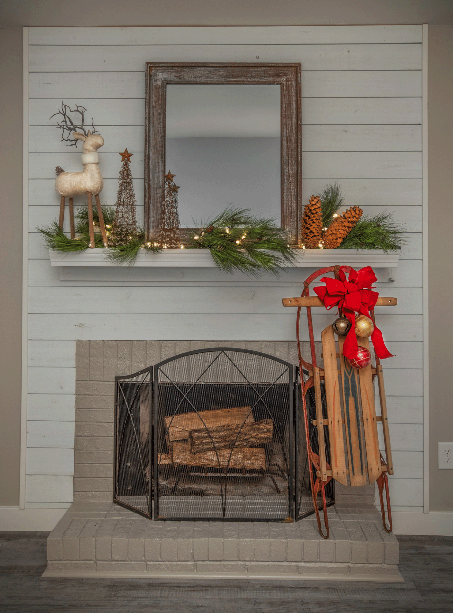 Fireplace mantle design with holiday decor, reindeer, mirror, pinecones, sled