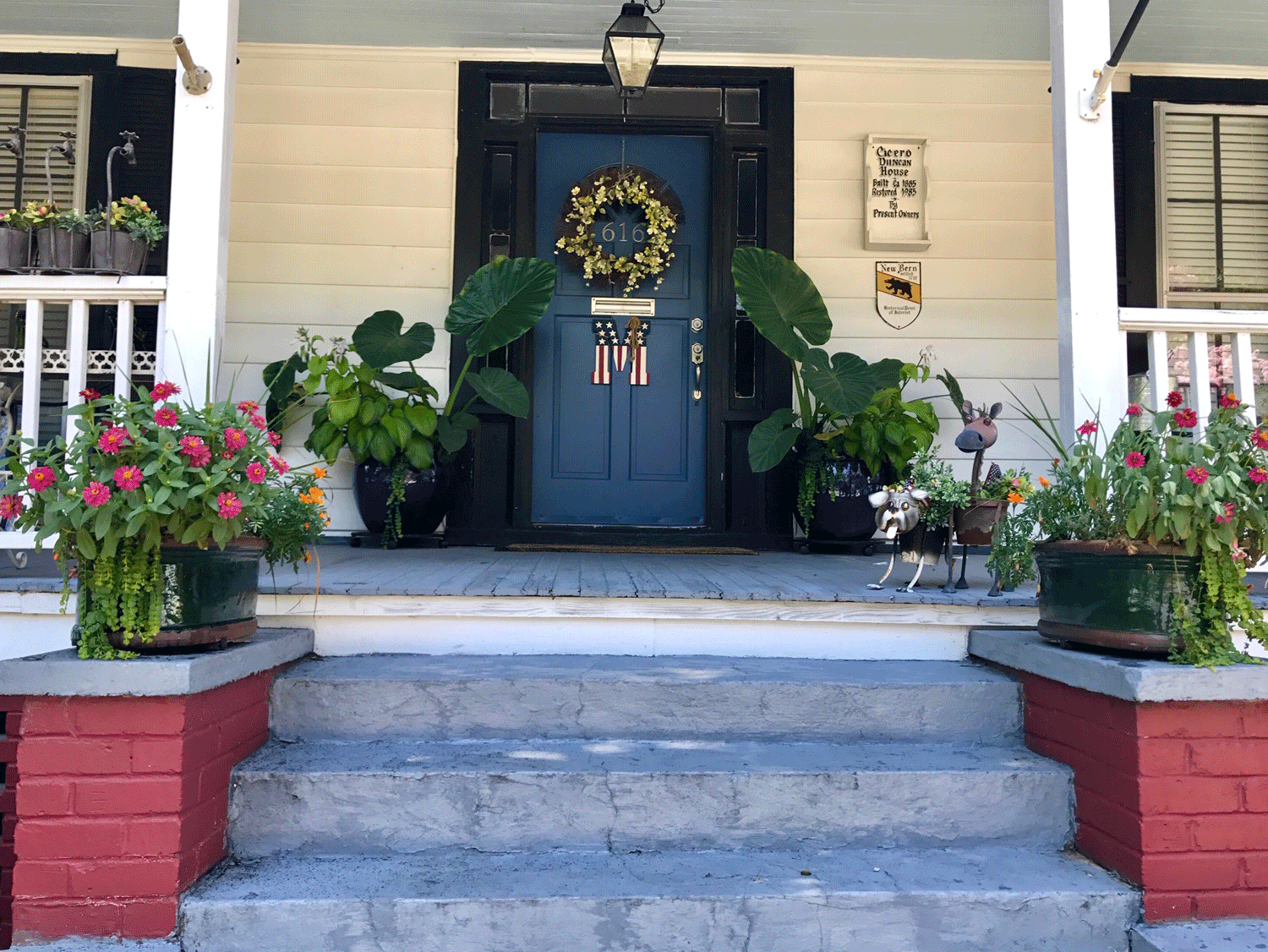 Front porch decor and container gardens flanking entry walkway