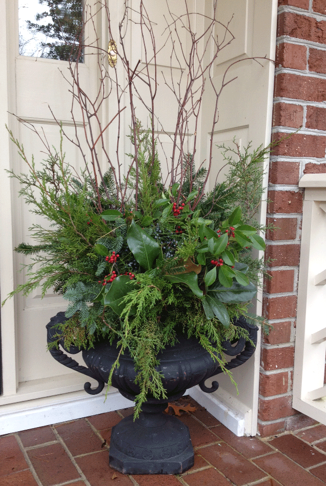 Urn on front porch with plant & branches