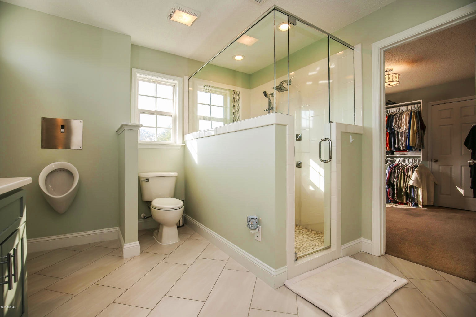 master bathroom with tiled shower and glass surround