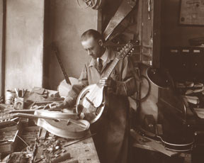 """This photo of Loar was published in many of Gibson's early catalogs and entitled """"R&D Department."""" It shows Lloyd with his 10-string mando-viola (shown below), at the Gibson factory on 225 Parsons Street, Kalamazoo, MI, ca.1924. From careful investigation of the building, it appears this photo was taken on the ground floor, along the western wall. Loar was about 38 years of age at the time this photo was taken. Click here for a close-up view of  Loar's workbench."""
