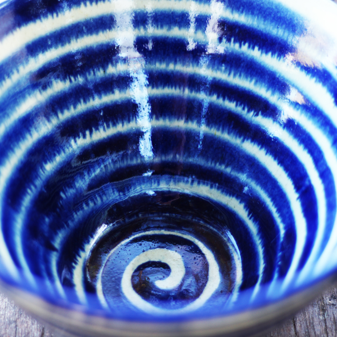 Handthrown bowl with blue spiral lines