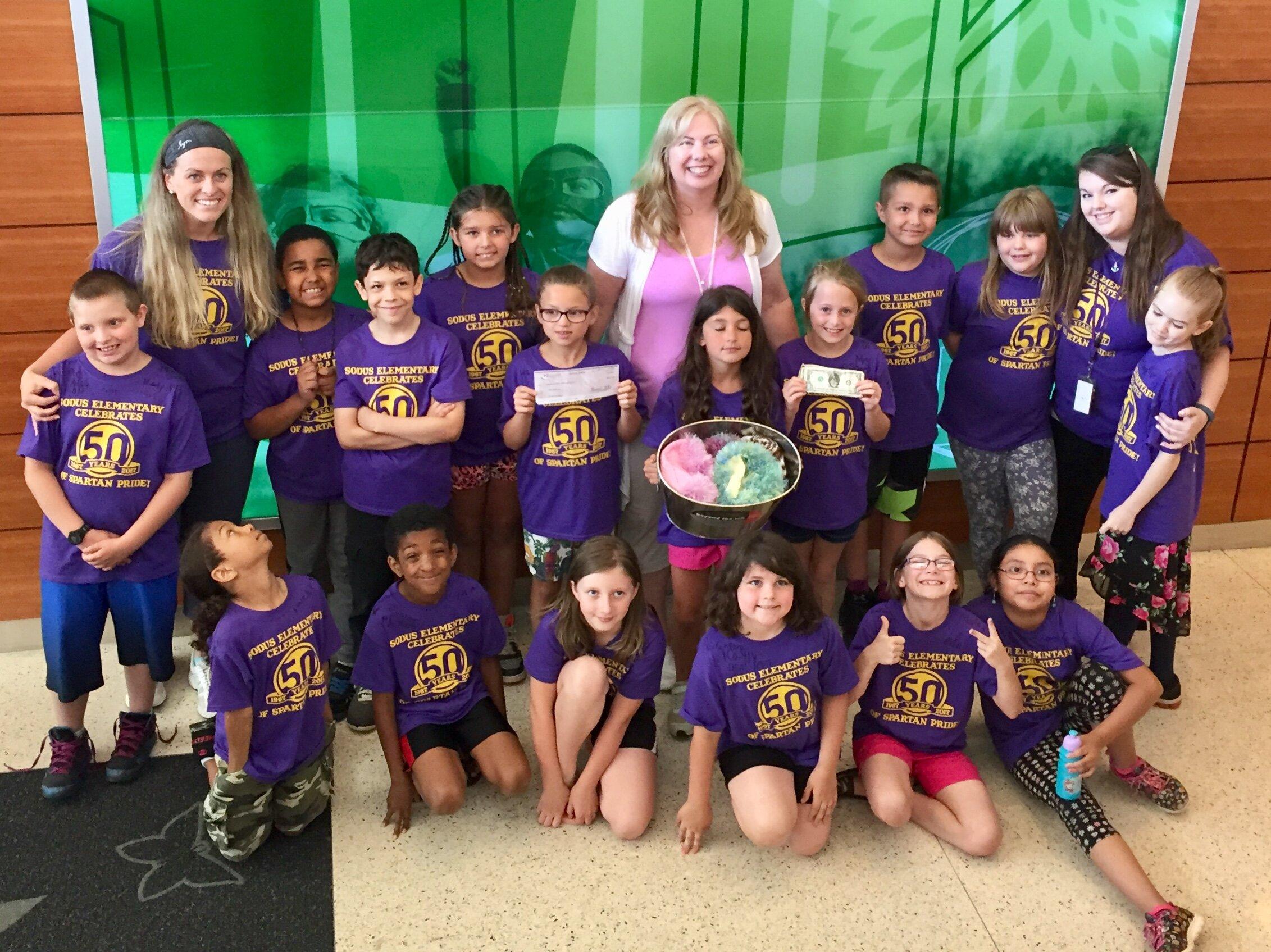 C.U.R.E. accepts a donation from Sodus Elementary School.