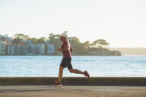 man running for weight loss in shorts outside along the beach front