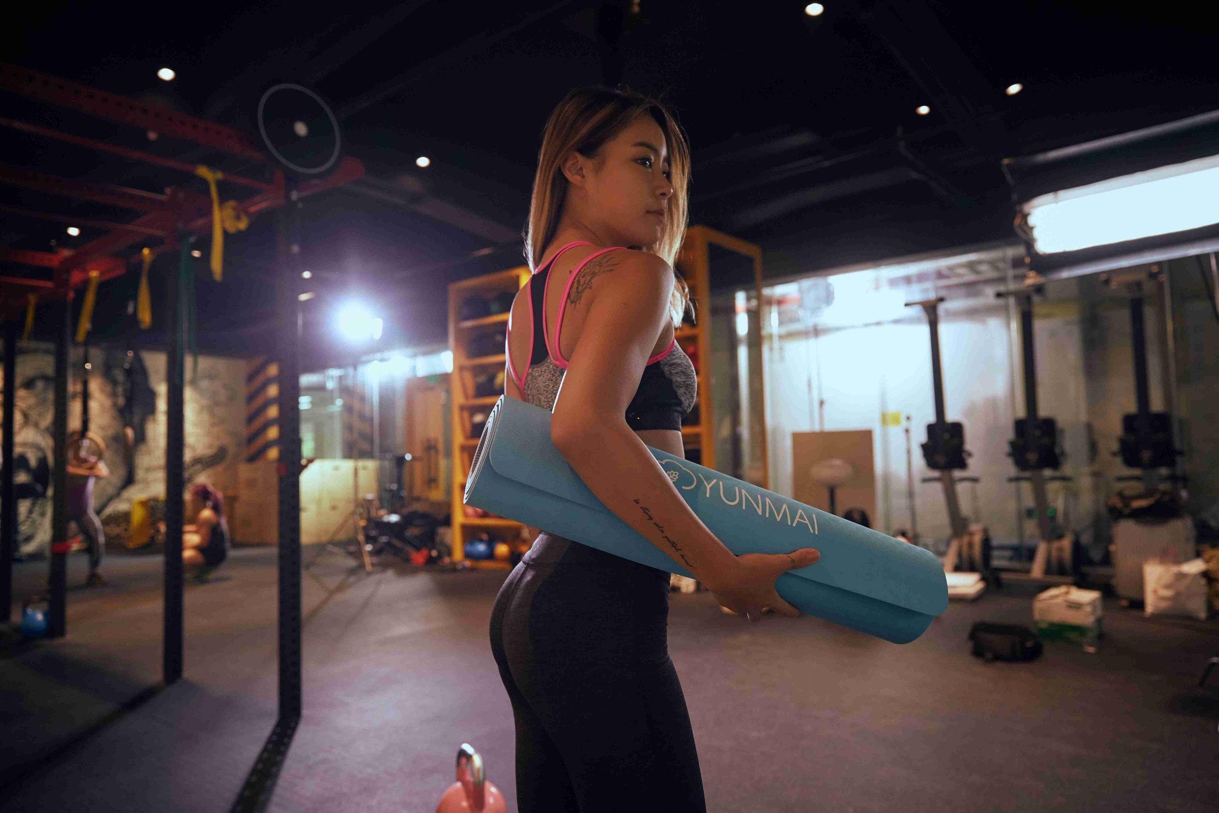 slim girl with yoga mat in the gym