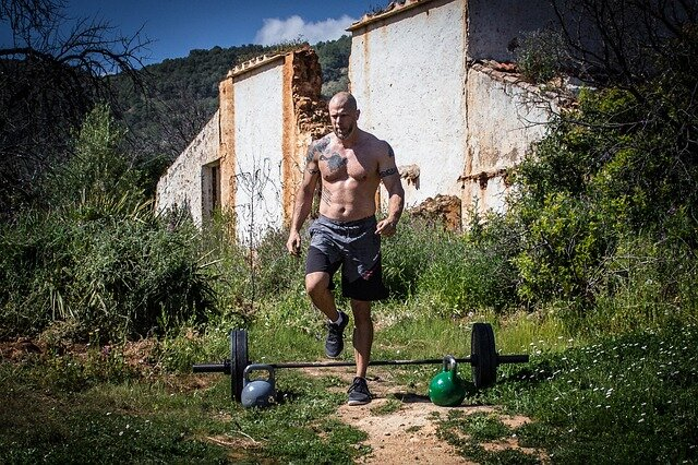 bald muscle man in backdoor garden with barbell and kettlebells
