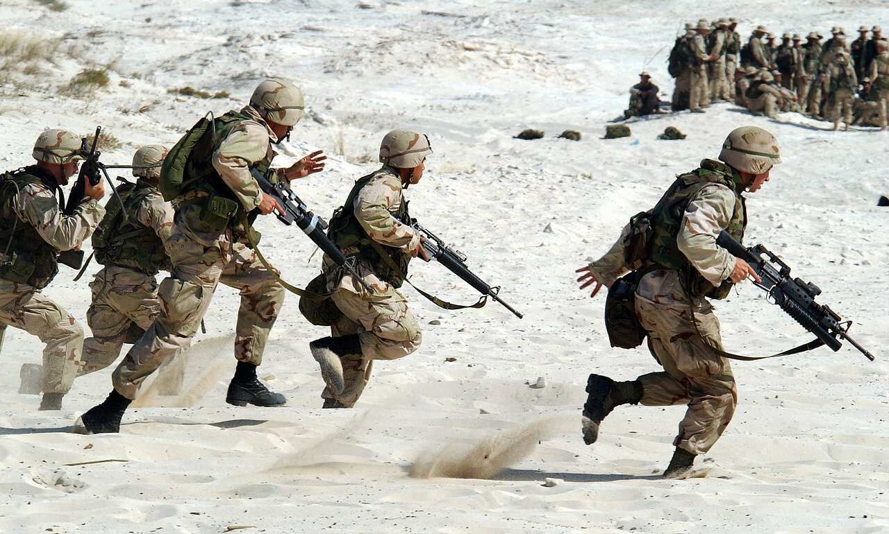 US soldiers in full gear running through white sand