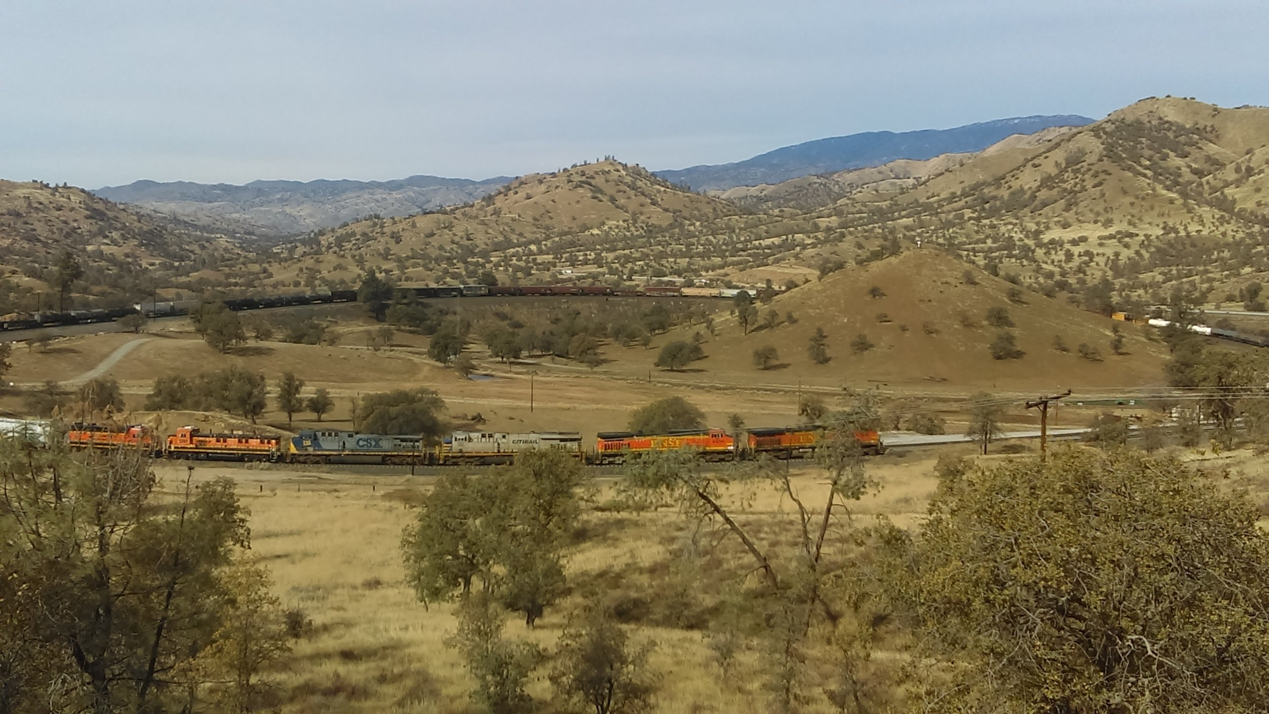Built in 1876, the Tehachapi Pass Line was the first railroad into Southern California. To keep the incline to a steady 2.2% grade, the line makes multiple sweeping curves and crosses over itself hallway up the grade to Tehachapi, in Walong, CA. In this photo, a BNSF manifest freight navigates the loop, crossing over itself in the process. Photo by Alex Lewis, 2018.