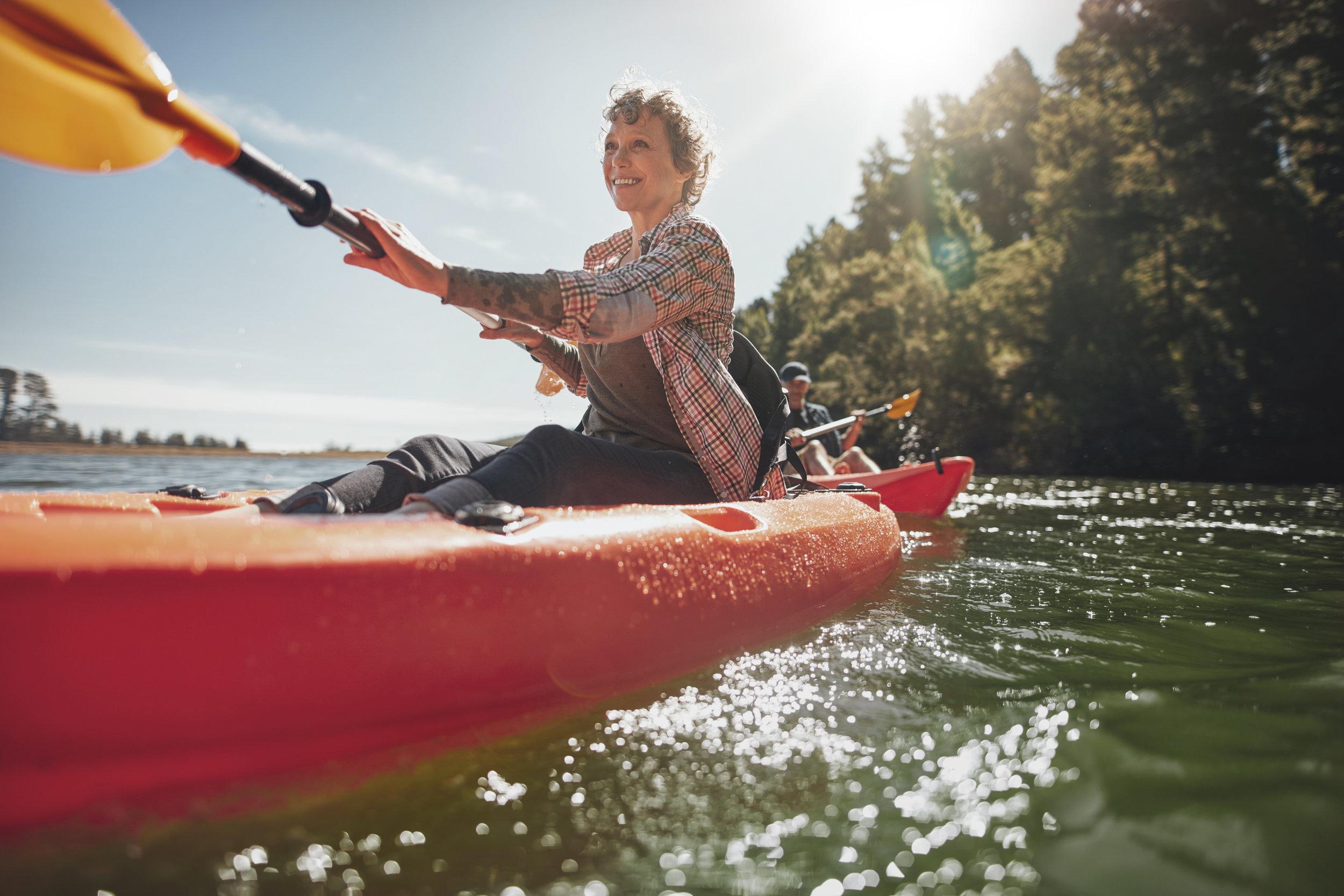senior-woman-canoeing-in-lake-on-a-summer-day-PZJK7NM.jpg