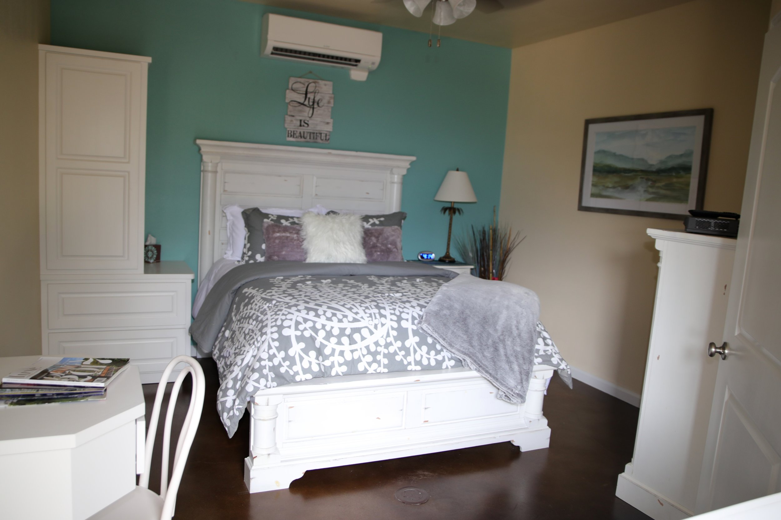 """The La Paz Room - """"La Paz"""" means peace in Spanish. This room can accommodate 2 guests.The La Paz Room includes a plush queen bed with touches of grey and floral whites, private walk-in bathroom with glass shower, mini refrigerator, cable & internet.Pricing Starting At $175 a night"""