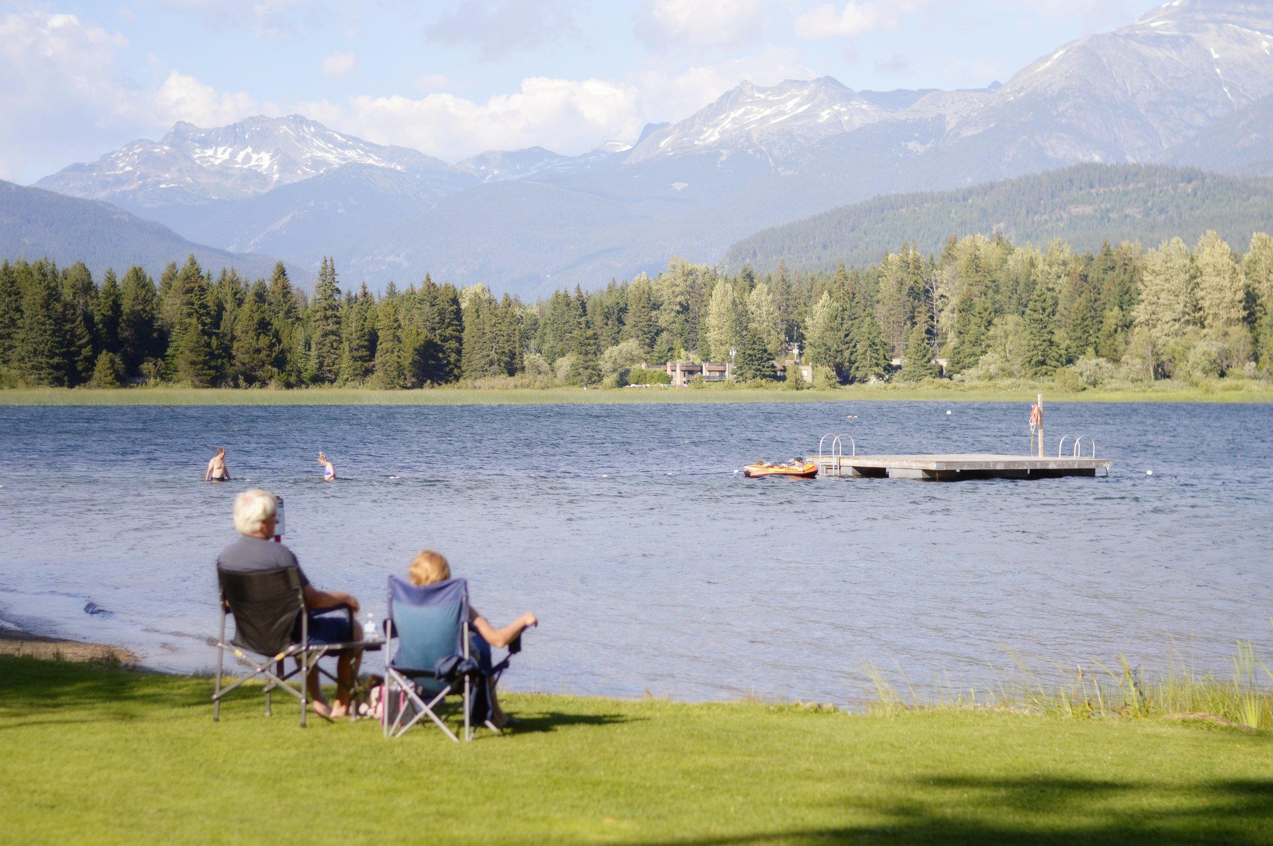 Retired couple sit by mountain lake enjoying the scenery.