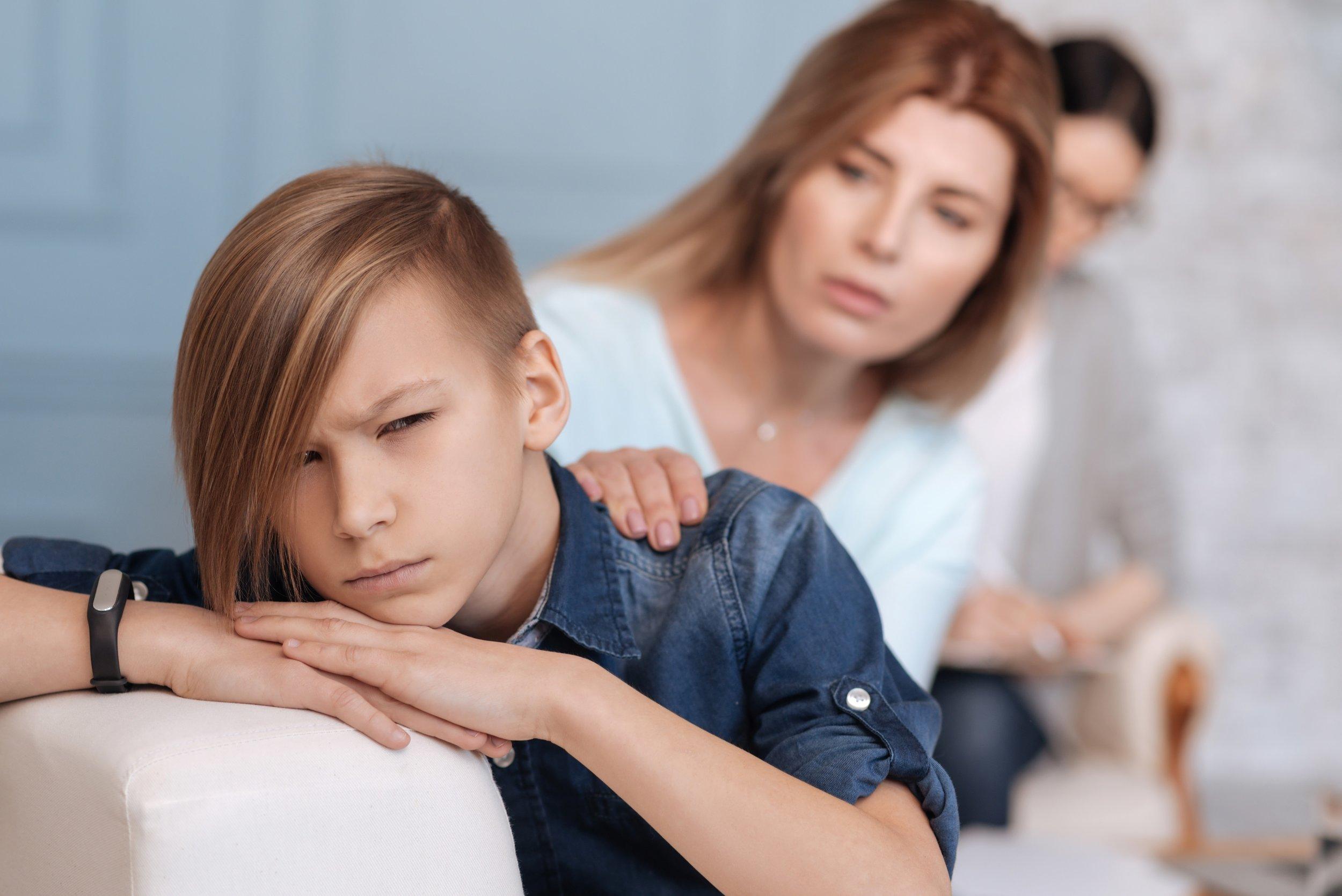 Mother puts hand on shoulder of depressed teenager.