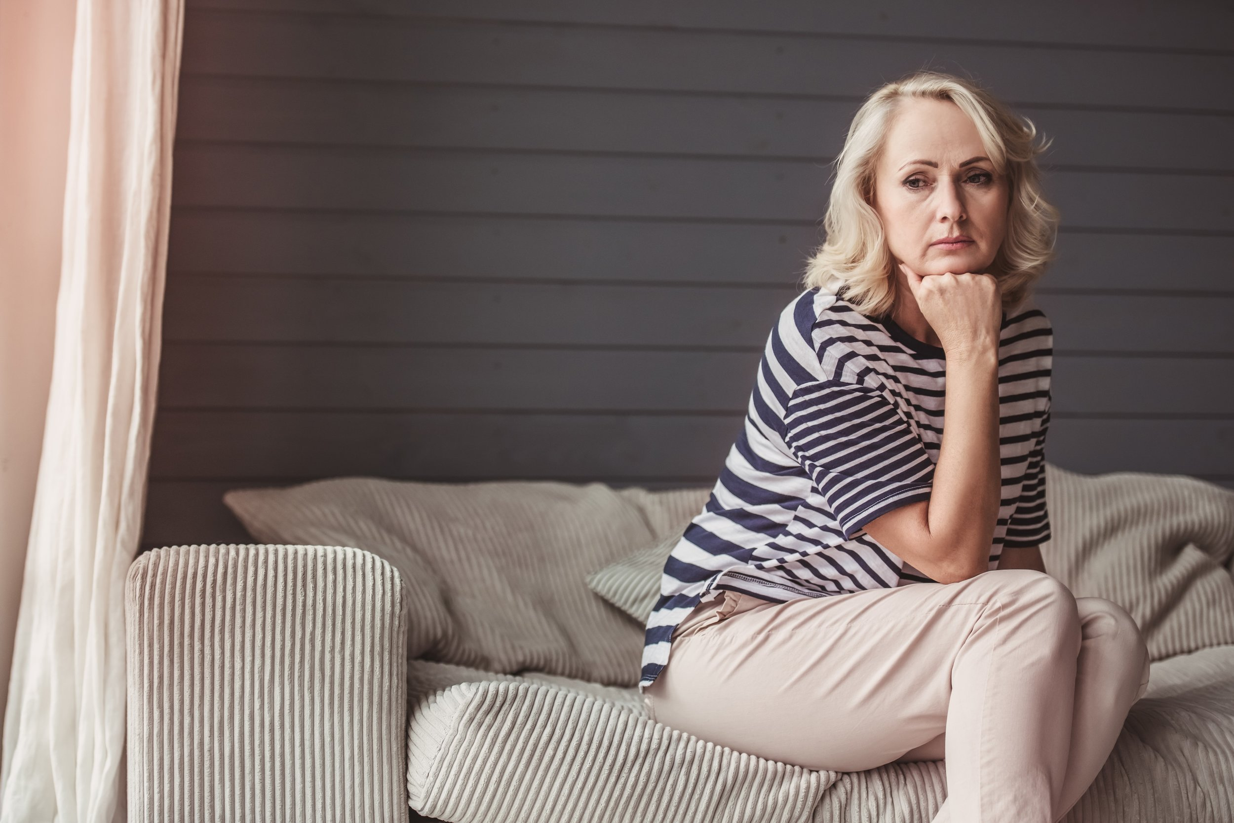 Senior woman sits on couch staring out window.