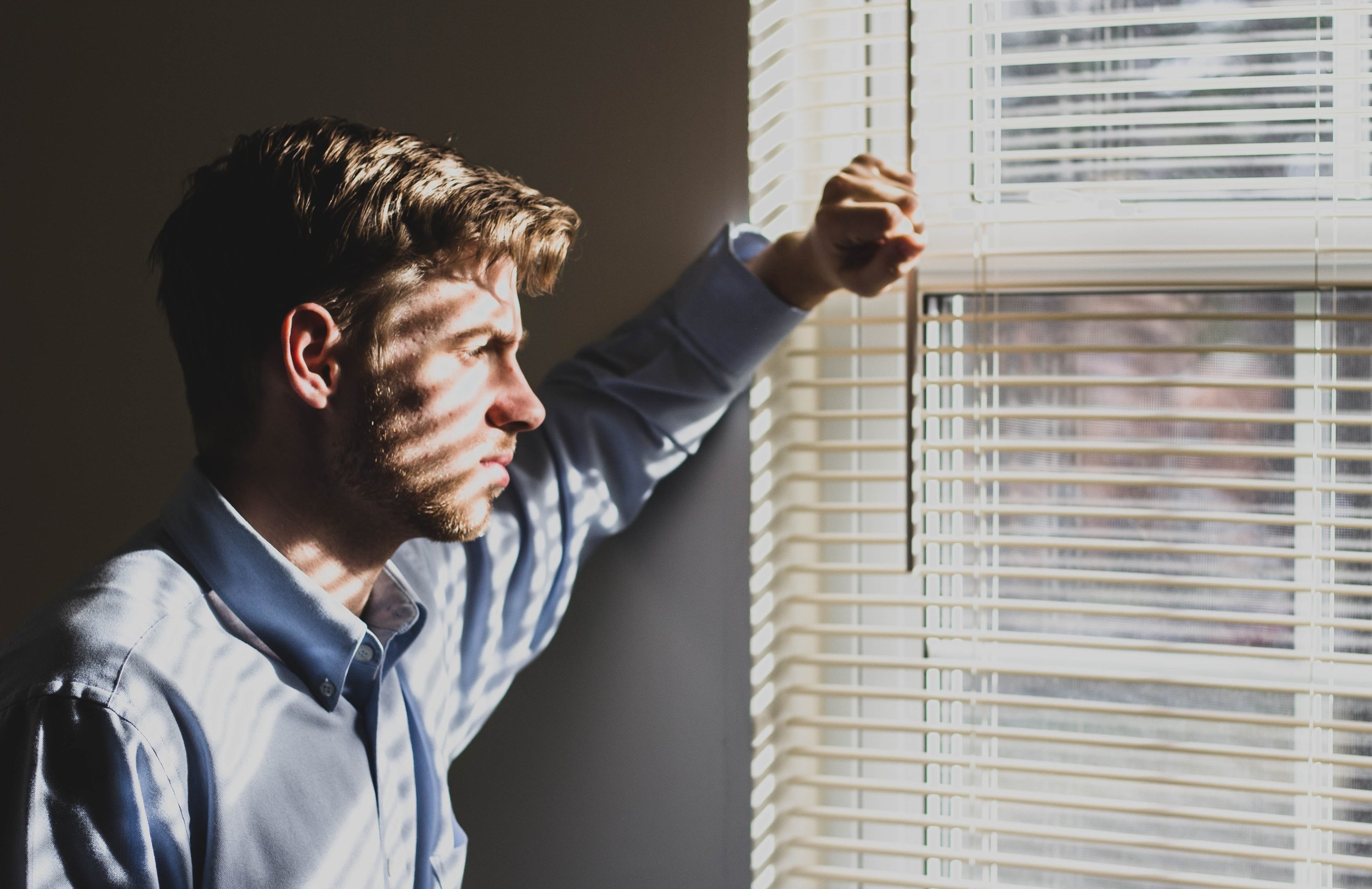 Depressed man in dark room gazes out of window.