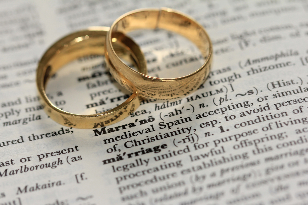 Wedding rings on a dictionary with word and definition of marriage.