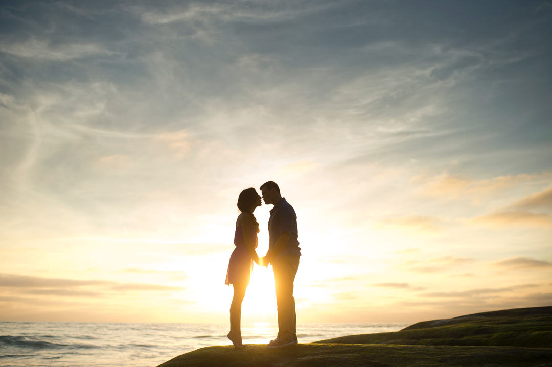 Romantic couple kissing in silhouette on the beach at sunset.