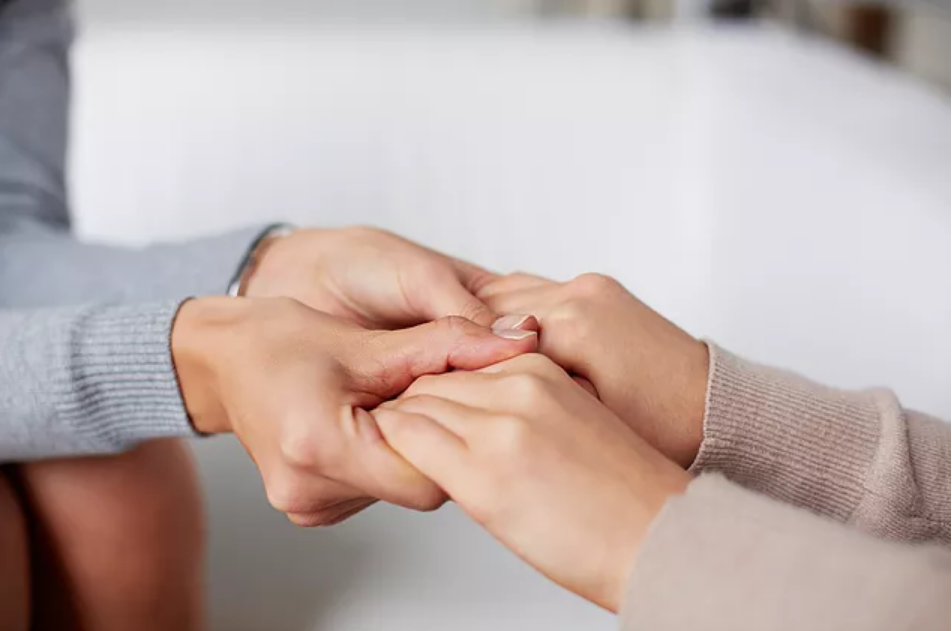Therapist holds hand of patient coping with a bipolar family member.