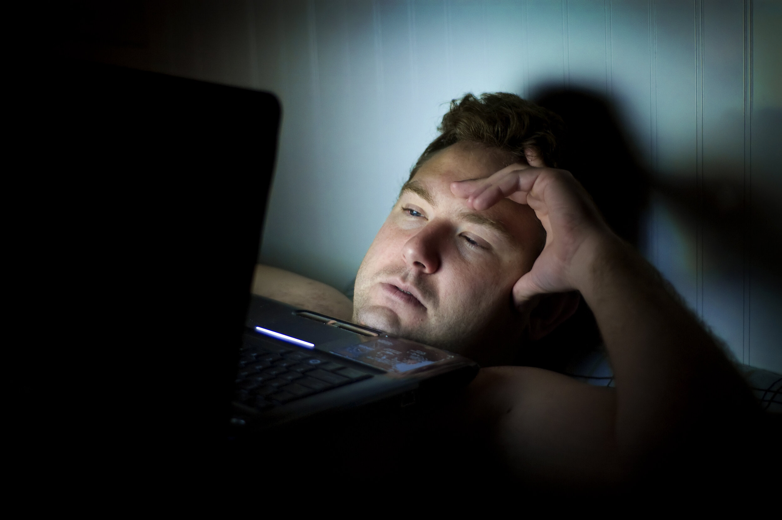 Man laying in bed in the dark with computer on his chest.