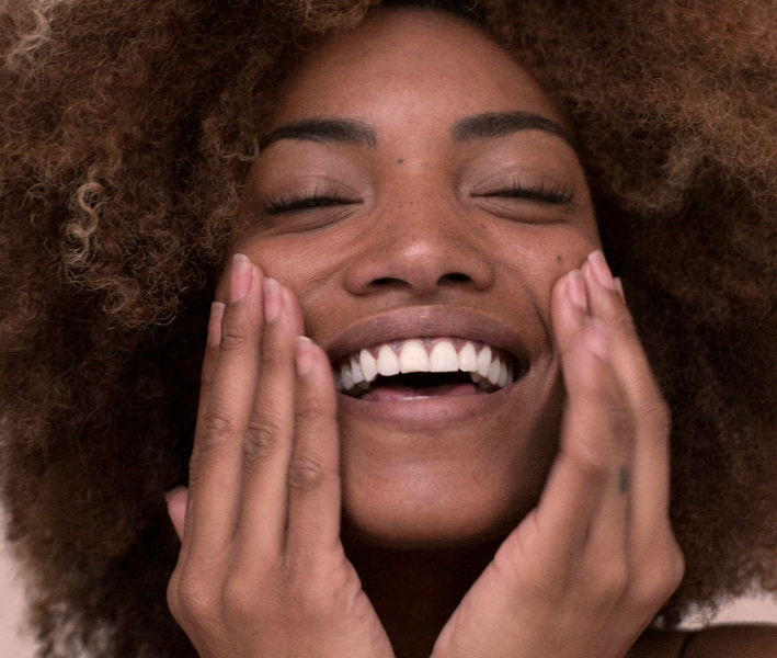 African American woman touching hands to her face happily smiling
