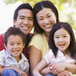 smiling-asian-family-of-four-outdoors-monkeybusinessimages.jpg