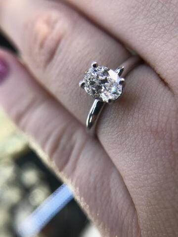 This custom solitaire engagement ring features an F VS1 oval Certified Canadian diamond. Its classic dainty design was designed by Secrète for a Northern Virginia couple in 2018.