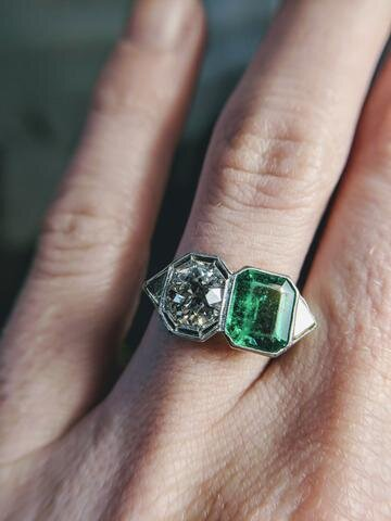 """This vintage two stone engagement ring from Secrète's DuPont Circle estate cabinet features a 1.01 ct F color VS1 Old Mine cut diamond next to a beautiful grass-green emerald. Two stones symbolize """"you and me."""""""