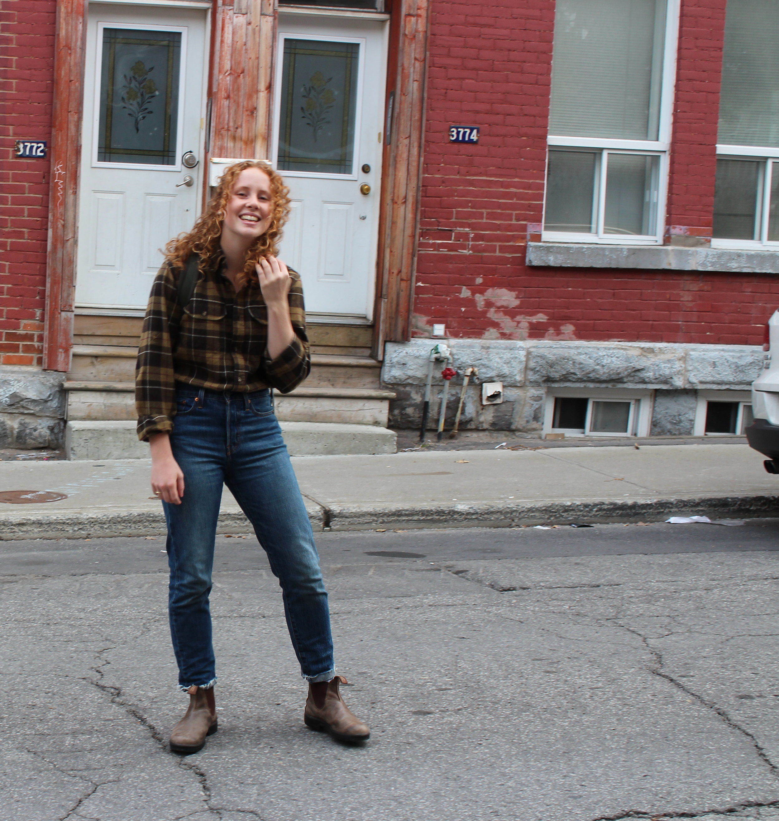 girl posing in front of house with jeans, flannel, and backpack