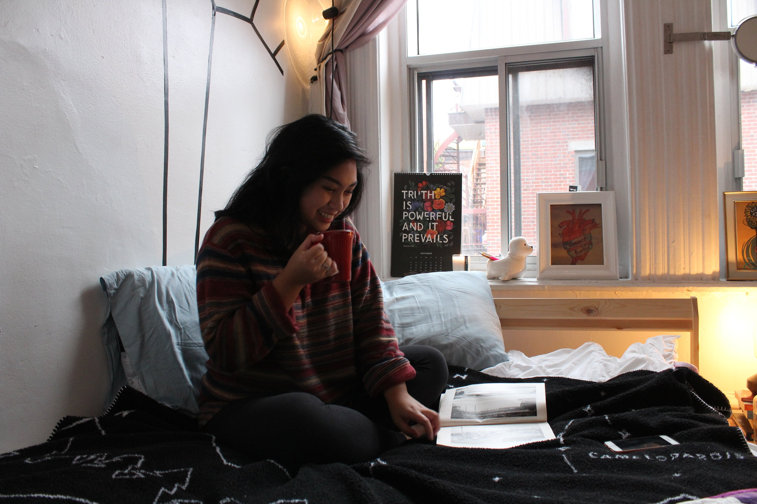 girl reading book on bed drinking tea