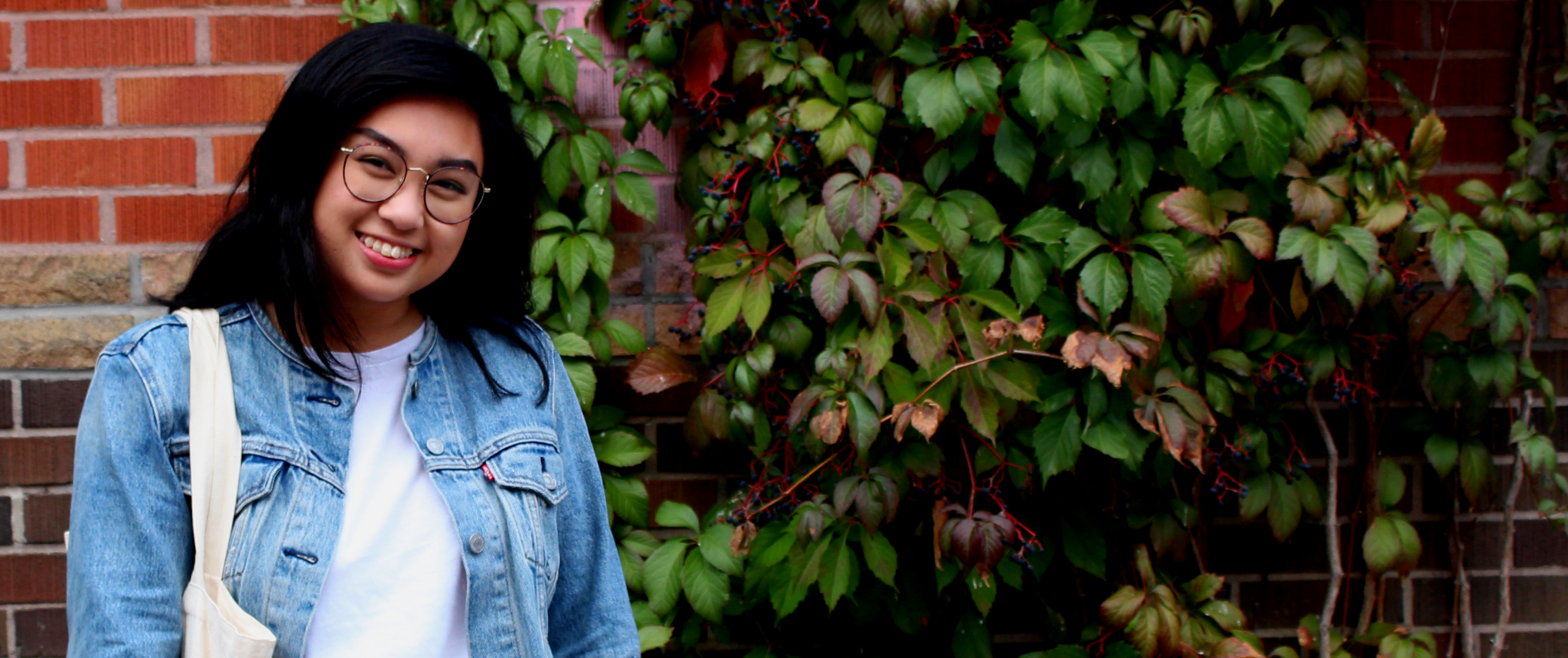 girl posing in jean jacket in front of brick wall with vines