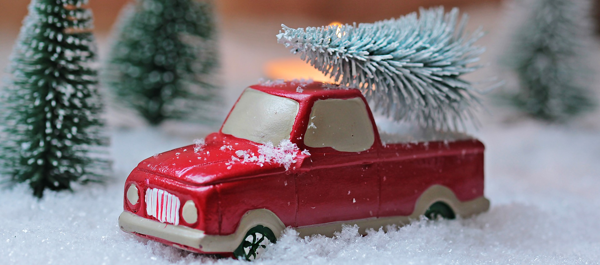 toy red truck in fake snow with miniature christmas trees