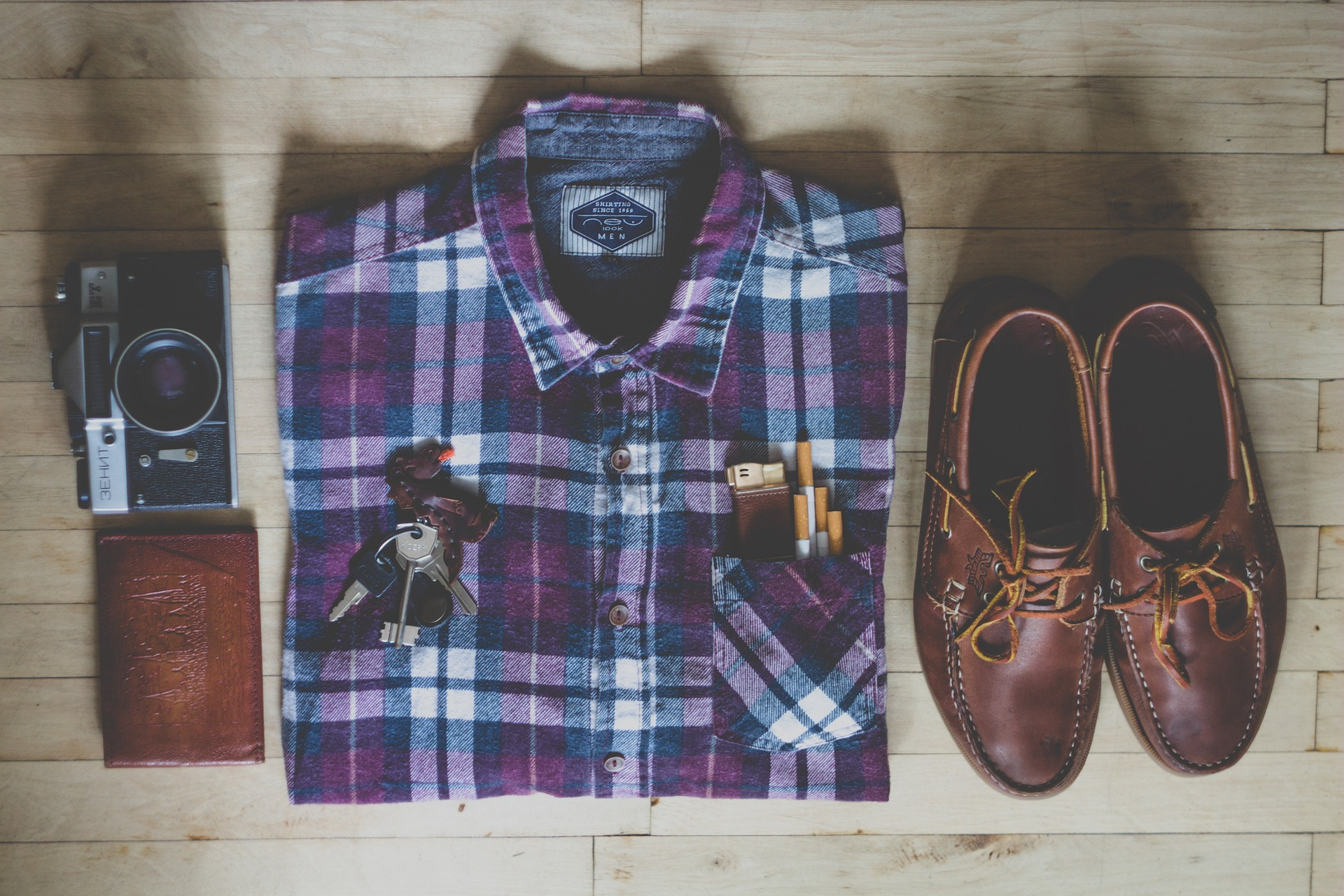 flatlay of flannel shirt, shoes, wallet, and camera