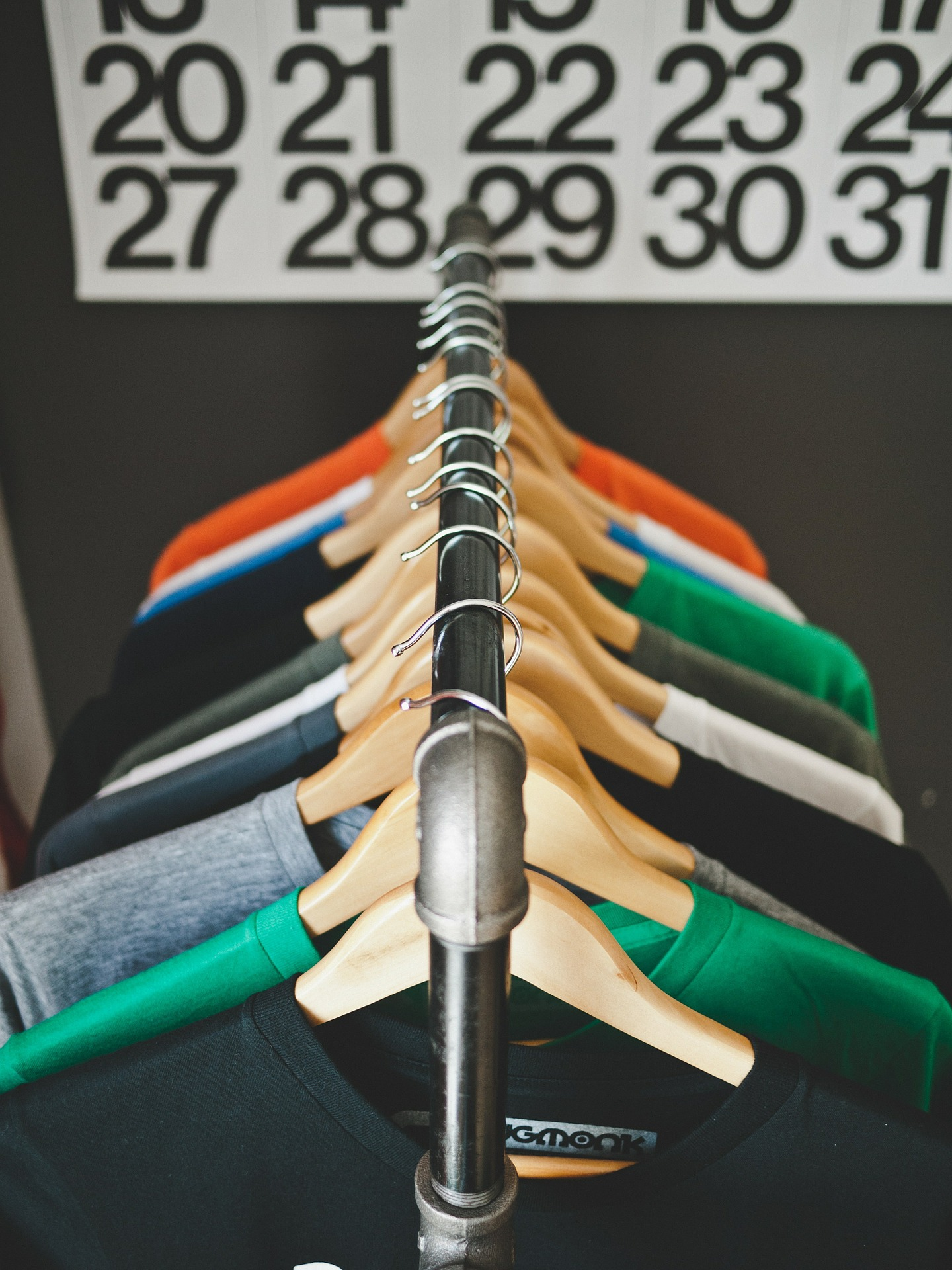 t-shirts on a clothing rack with calendar in background