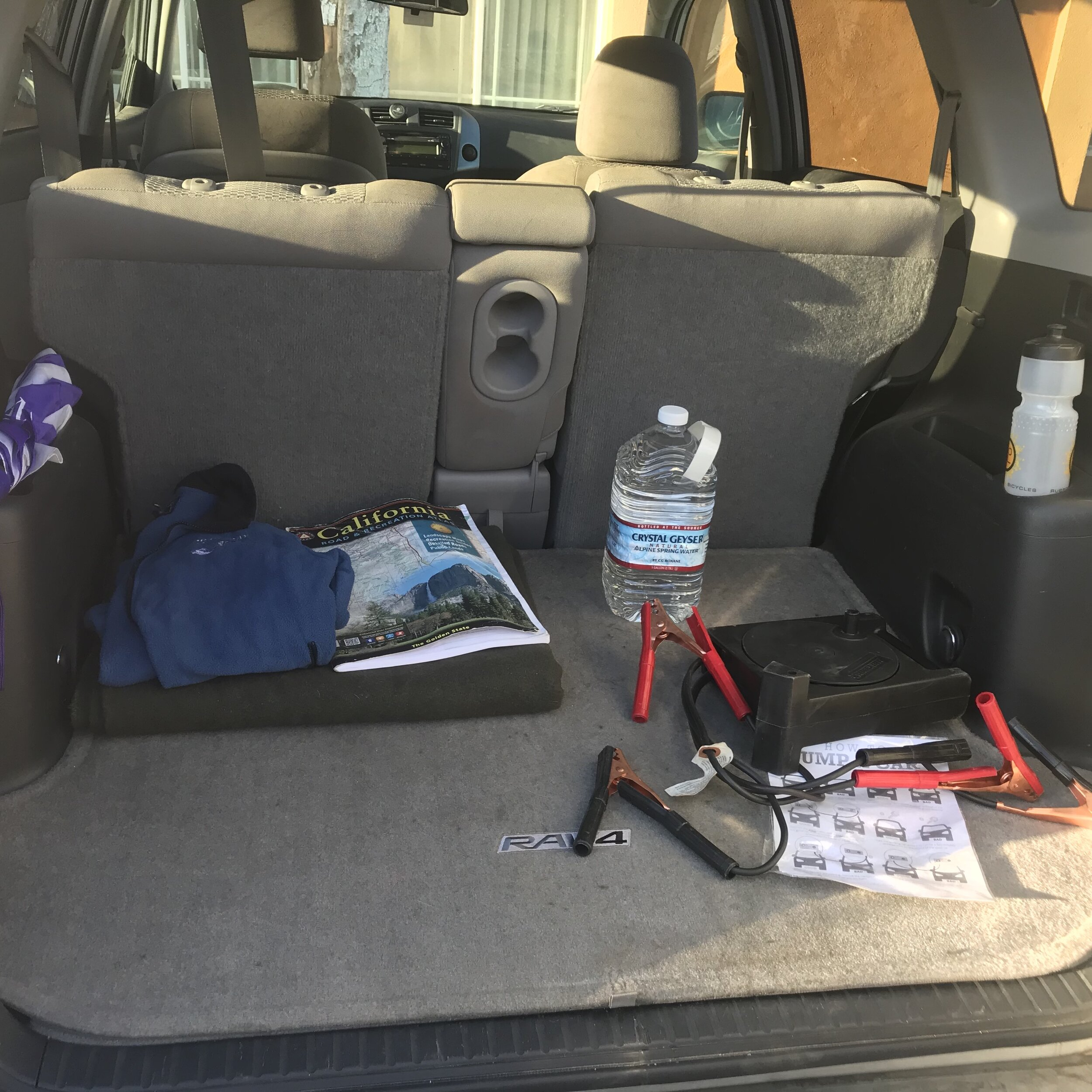 Wool blanket, fleece jacket, state maps, umbrella, water, & jumper cables with instructions