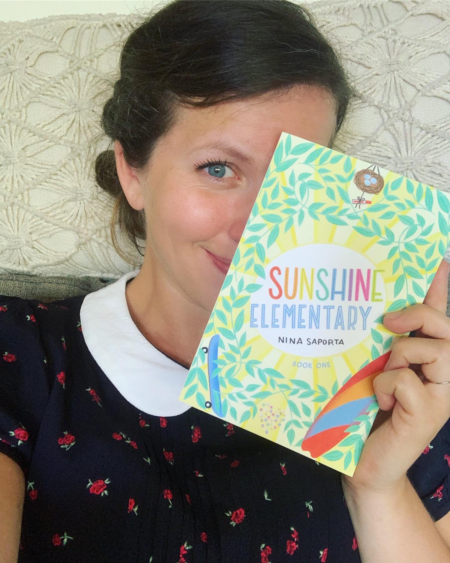 Author Nina Saporta holding an early copy of  Sunshine Elementary