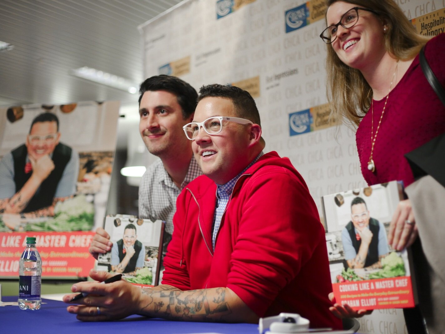 Two MIchelin Star Chef Graham Elliot signing books with guests at George Brown College's Centre for Hospitality & Culinary Arts