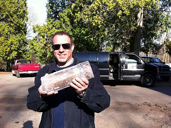 "Time Capsule Reveals ""Grapeshot""    When the barrel came up last fall—along with old skulls and bones—local historian Rob Greenberg (pictured holding a capsule) began to suspect it contained a time capsule. He eventually  got the city bomb squad to X-ray the concrete lump , revealing enough evidence that Bellantoni and others worked to scan the concrete further, and crack it open to find the capsules.  At the press conference Monday afternoon, Drew Days, a Proprietor of the Green, publicly thanked Greenberg for his dogged pursuit of his time-capsule theory, which ""kept us focused"" on the possibility. ( He barred Greenberg earlier in the day from watching  the capsules being opened.)  Read the article in the New Haven Independent   Time Capsule Reveals ""Grapeshot"""