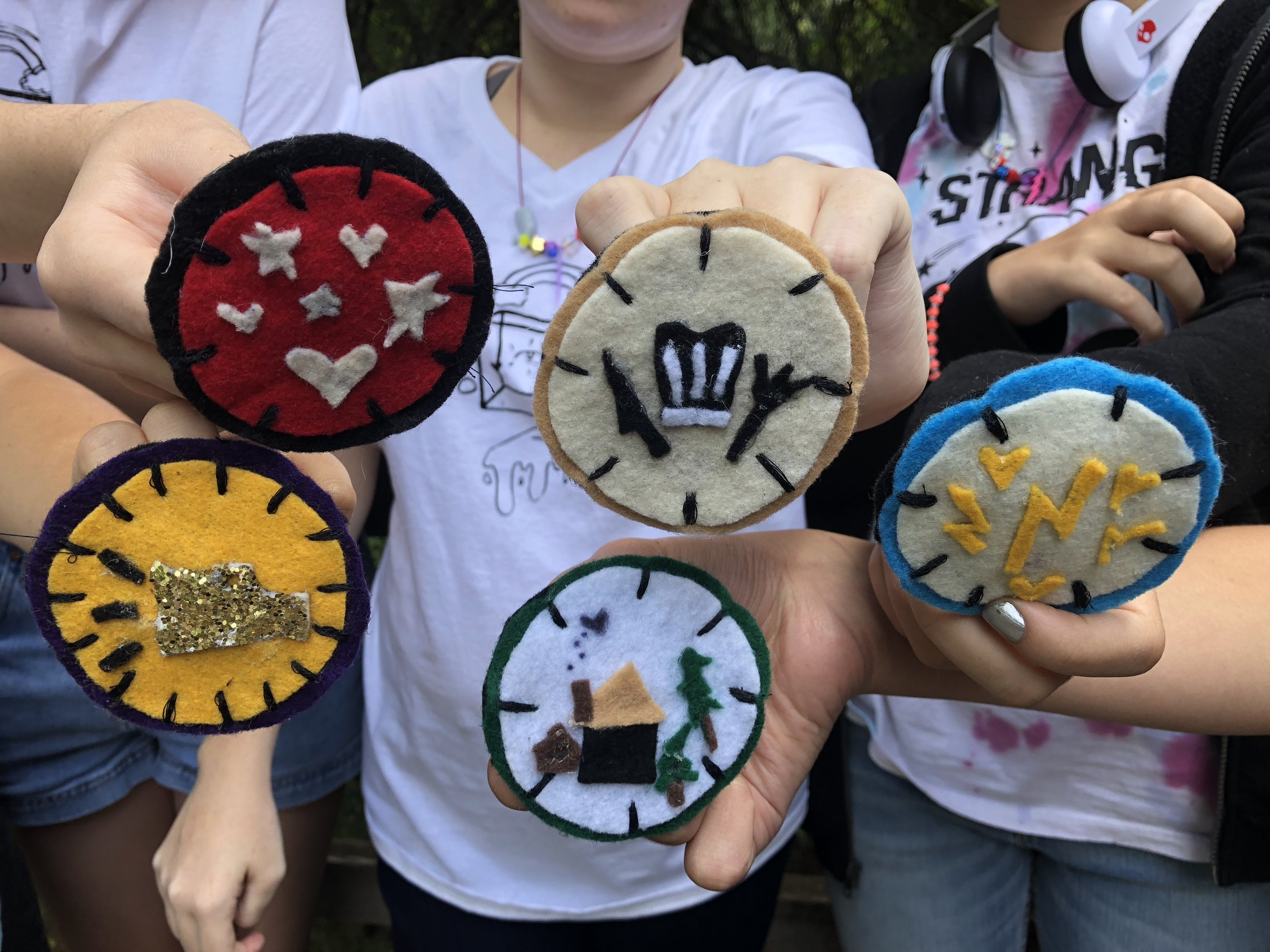 Youth showing off their badges at Glitter Camp 2018