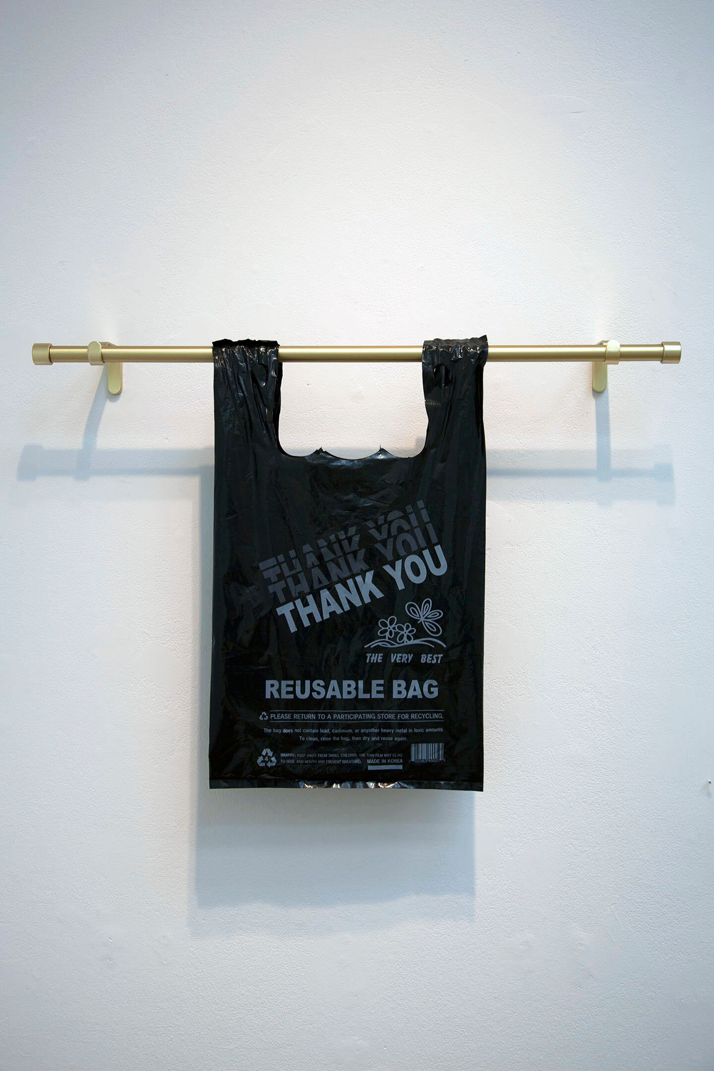 Thank You Thank You Thank You Thank You , 2019, reusable plastic bag, brushed brass curtain rod, 21 x 29½ x 4 inches.