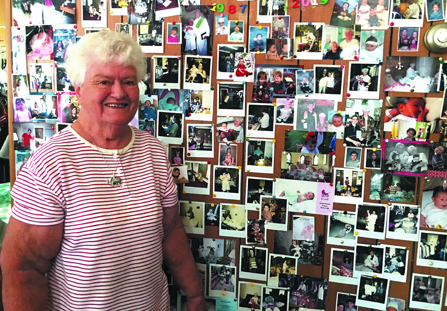 FOR THE KIDS : Dot Bottaro stands next to a wall of photos of youngsters her efforts as coordinator of the Children's Thrift Shop at St. Peter's Catholic Church in Liberty have helped. Bottaro has run the shop for 32 years.  Emily Ball photo