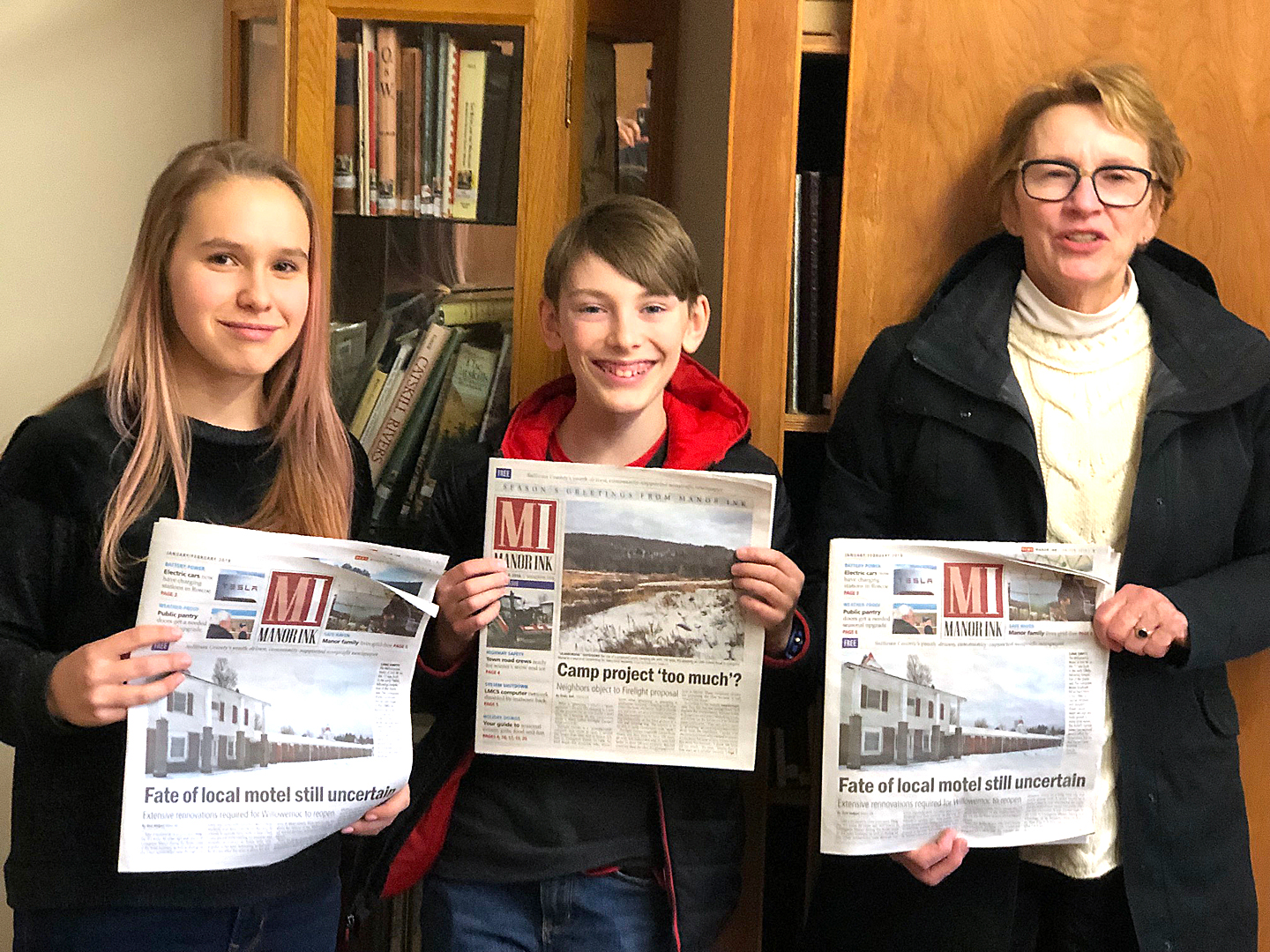 CONNECTING   Manor Ink  reporters Emily Ball and Edward Lundquist share a copy of the paper with Assemblywoman Aileen Gunther at the Livingston Manor Free Library.  Art Steinhauer photo