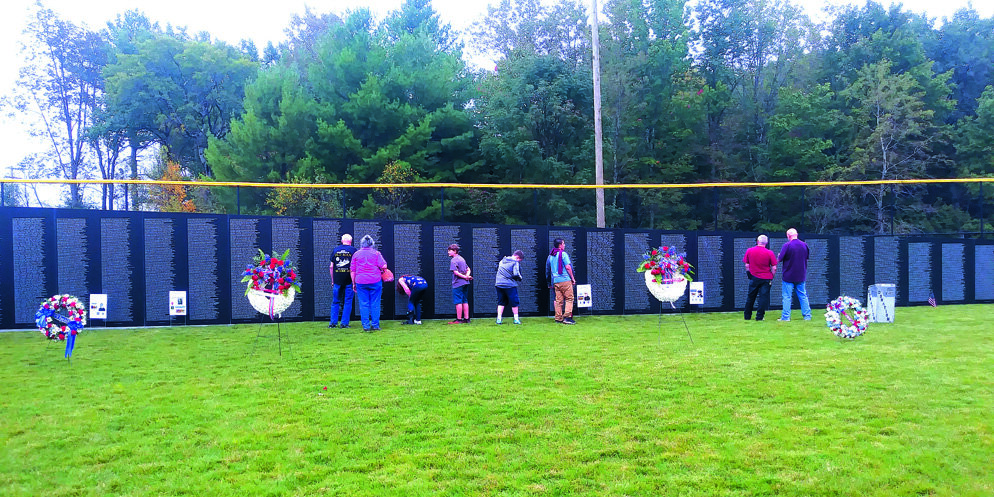 SOBERING  Students from Livingston Manor Central School view the thousands of names that cover the wall of the traveling version of the Washington, DC, Vietnam Veterans Memorial. The memorial was erected in Rock Hill and later traveled to Monticello. Luca Larizzati photo