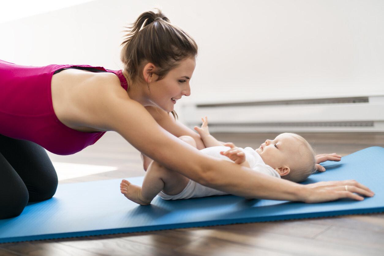 Woman doing yoga with newborn baby