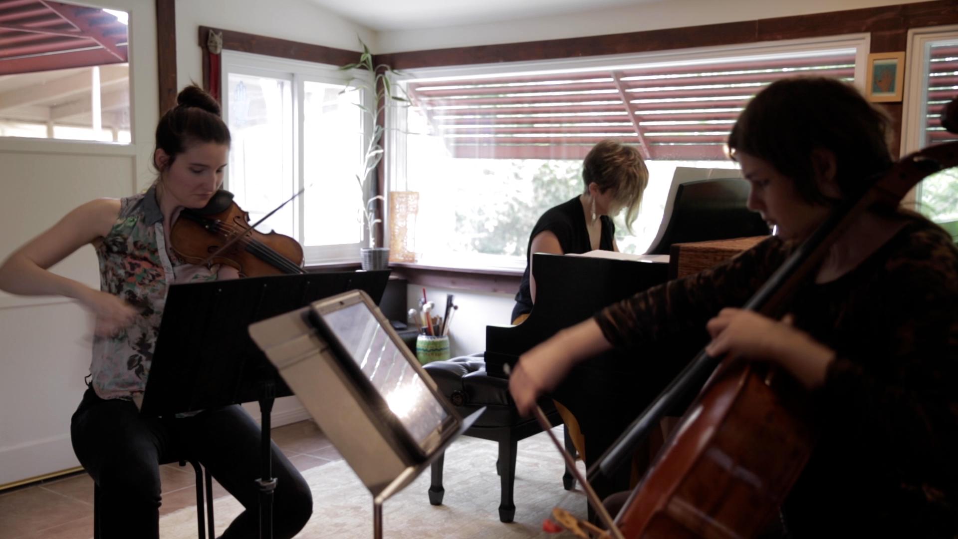 Emily Call, violin, Basia Bochenek, piano and Betsy Rettig, cello rehearse  Cambridge Sonata .