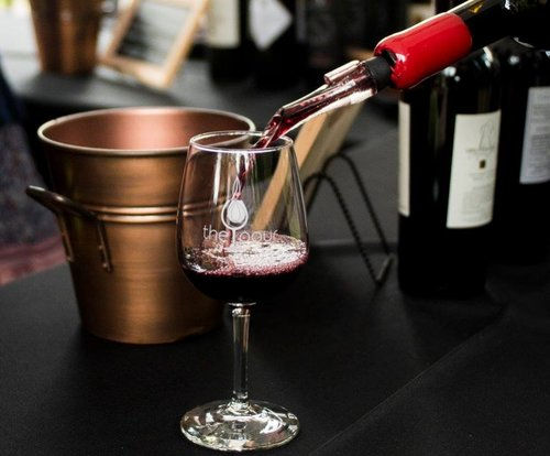 A photo of red wine being poured into a glass. Behind is a copper bucket and two bottles of wine.