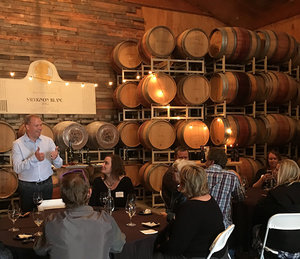 A photo of a small group of people tasting wine at a table and talking with stacks of wine barrels behind them.