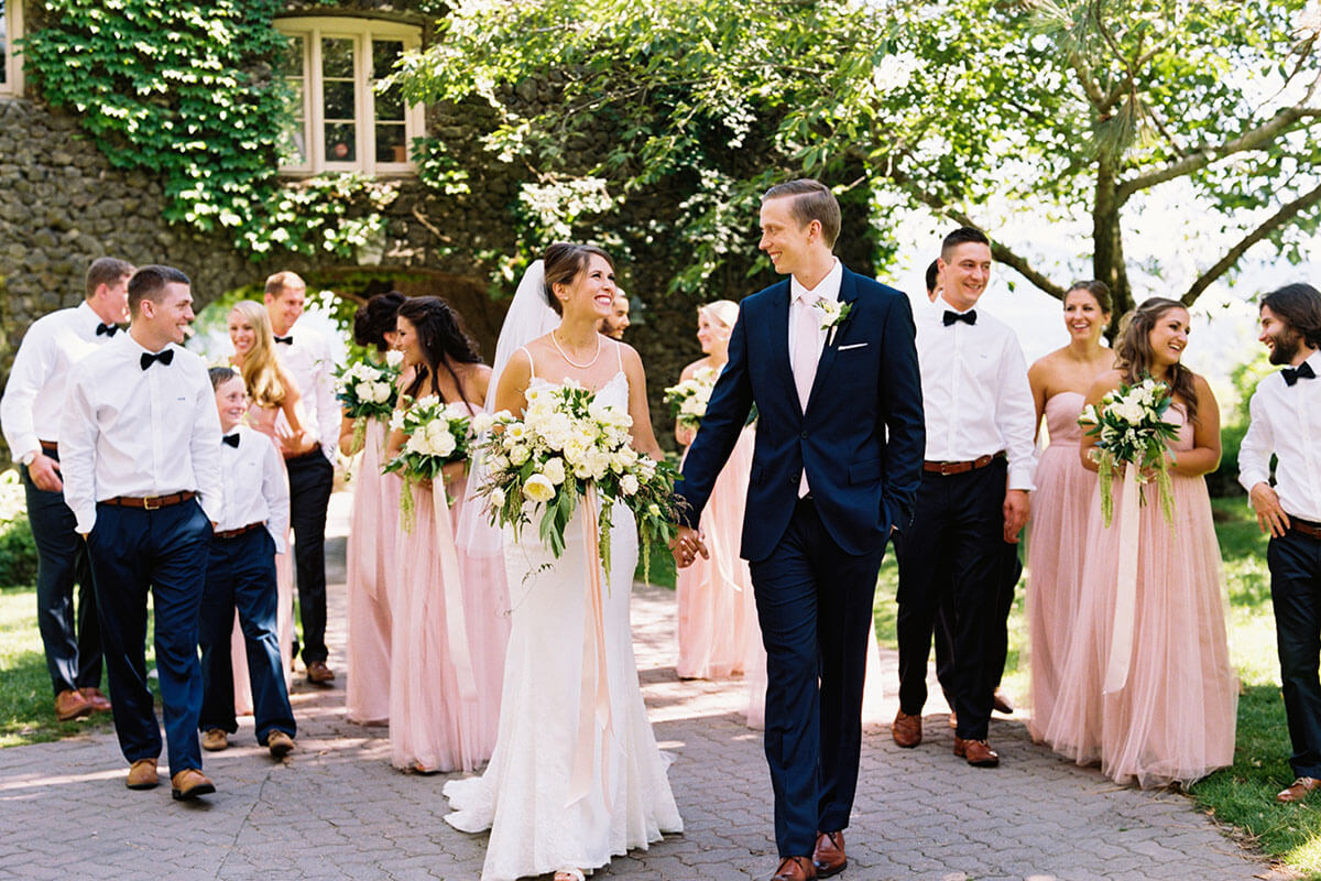 a photo of a wedding couple staring at each other and the wedding party following