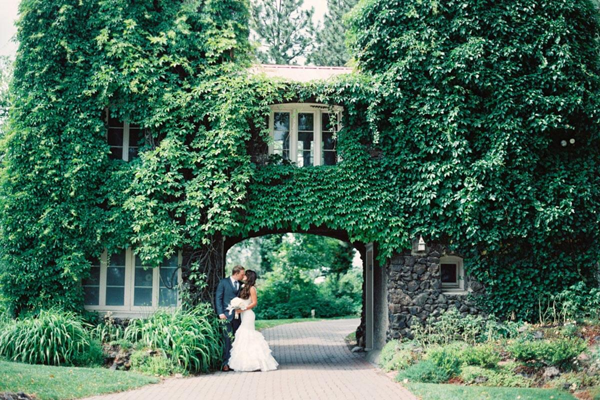 A photo of a bride and groom kissing in front of the gatehouse with overgrown greenery