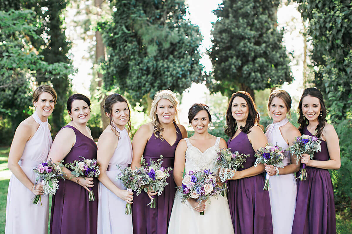 A photo of a bride and her bridesmaids in white and purple with flowers