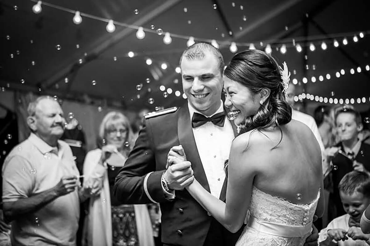 A black and white photo of a bride and groom smiling as they dance in the wedding tent with friends and friends behind them