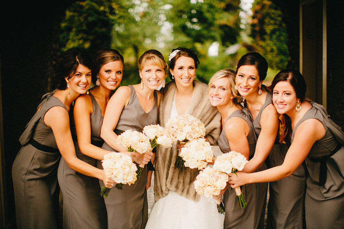 A photo of a bride and her bridesmaids holding their flowers in the center of the group